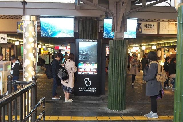 写真中央に見えるのが、嵐山駅に設置されている大型のデジタルサイネージ。縦長の55インチ 4Kタッチパネルと2枚の広告配信用モニター(上面左右に設置)で構成されている