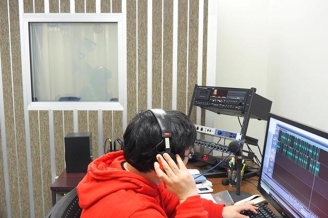 PCで録音トラックを確認するディレクターの伊藤氏(手前)と、曇りガラスの向こうに声優の永吉さん