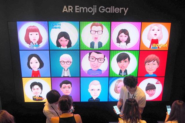 AR Emoji GALLERYで自分のアバターをつくる来場者たち。できあがると壁のモニターに追加される