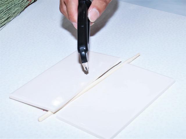 タイルに切り込みを入れ、下に割り箸を置き上から押すときれいに割れた【撮影:小宮山あきの】